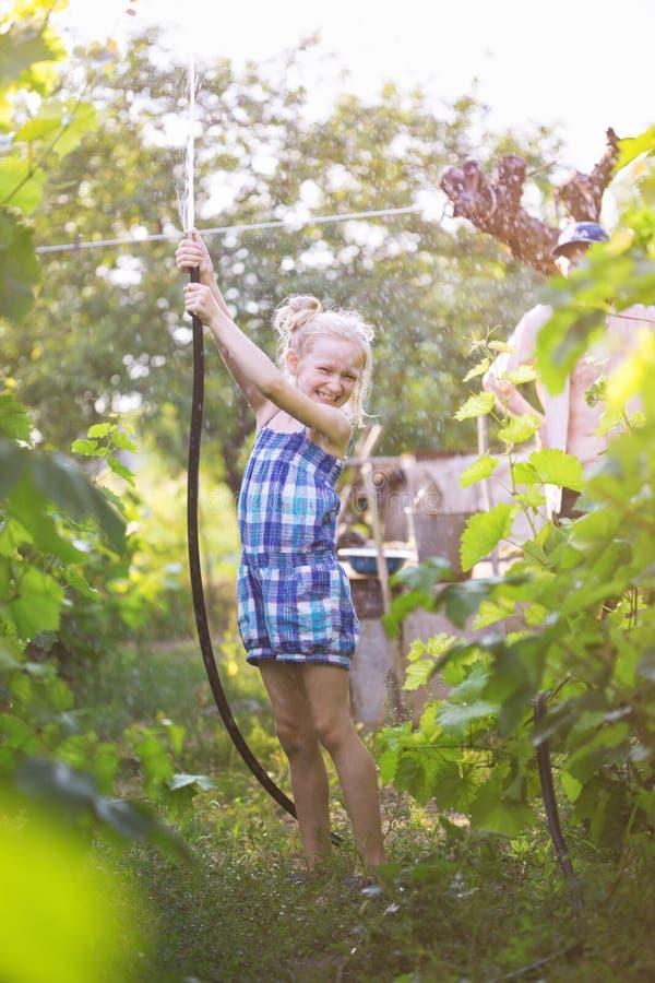 Liten flicka som har gyckel i trädgården arkivfoto