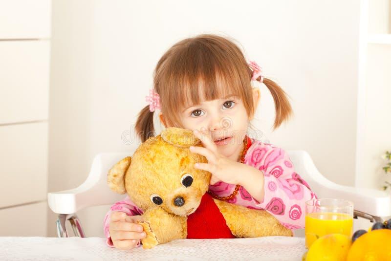 Liten flicka som har gyckel med den flotta björnleksaken arkivbilder