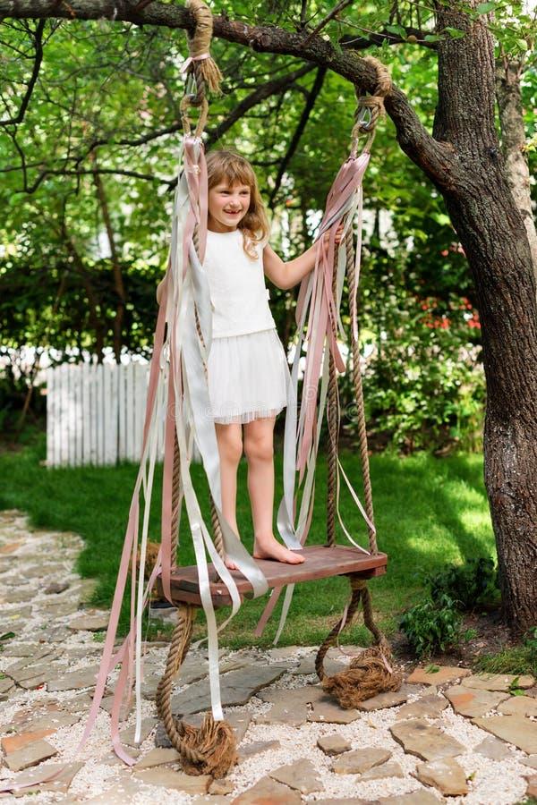 Liten flicka som har gyckel på en utomhus- gunga Barn som spelar, trädgårds- lekplats royaltyfria bilder
