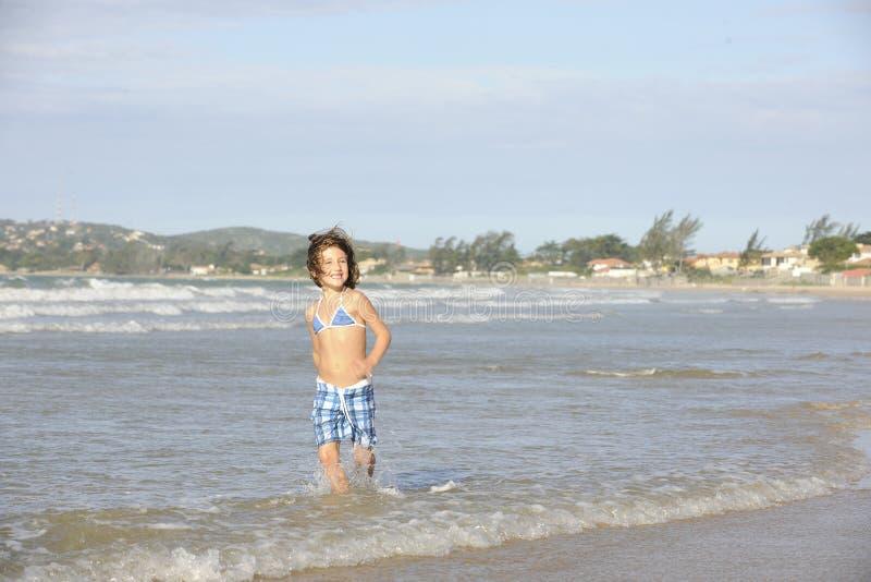 Liten flicka som har gyckel på stranden royaltyfria foton