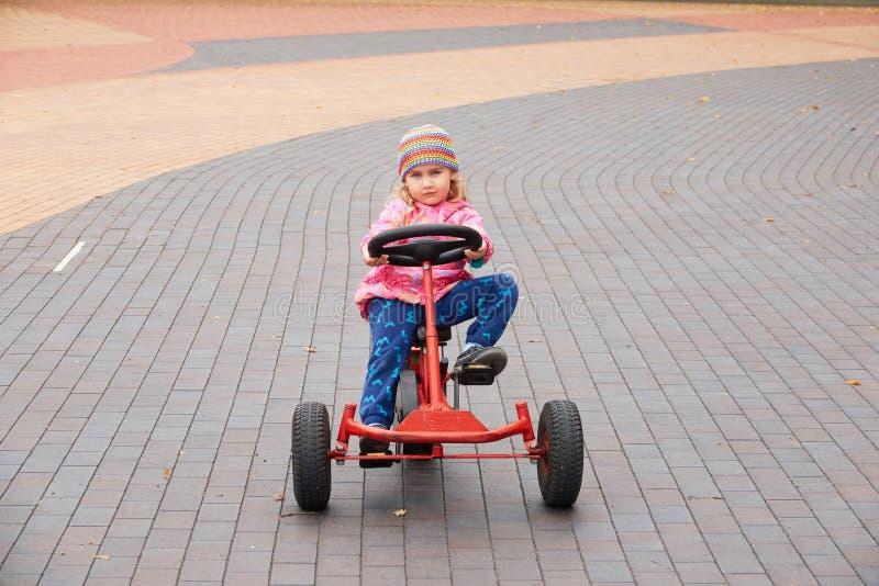 Liten flicka som har gyckel som kör en pedal- bil i dag fotografering för bildbyråer