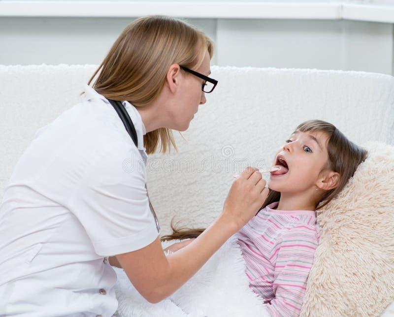 Liten flicka som har hans hals att undersökas av den vård- professionelln royaltyfri fotografi