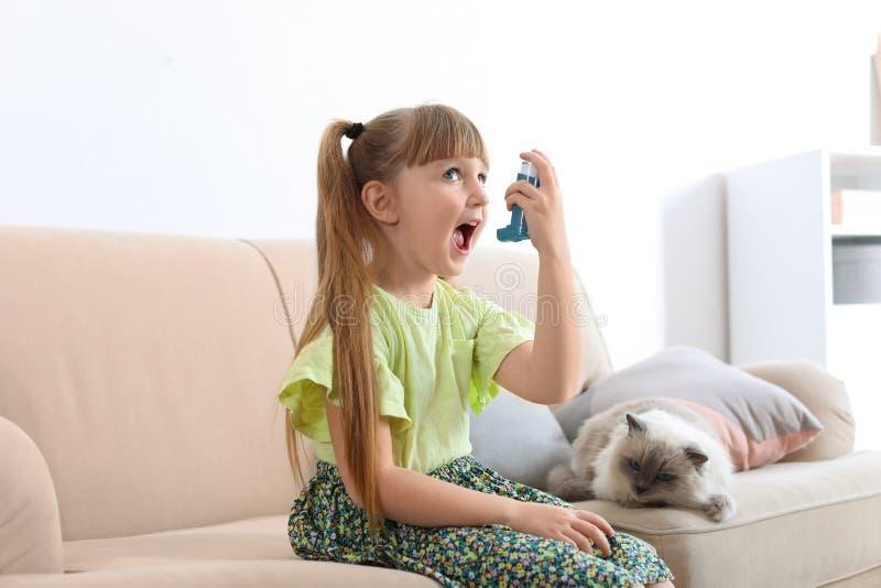 Liten flicka som hemma använder astmainhalatorn nära katt arkivbilder