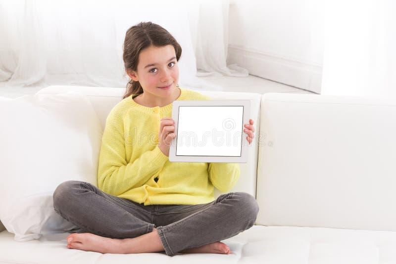 Liten flicka som hemma använder den digitala minnestavlan på soffan fotografering för bildbyråer