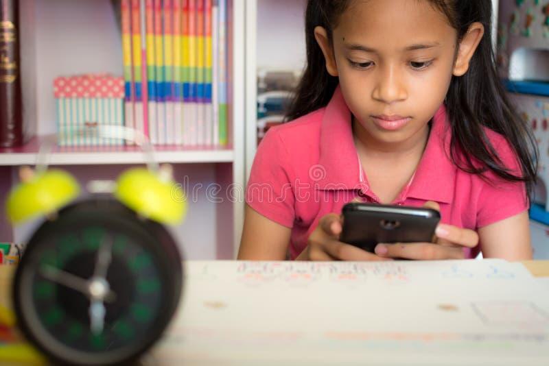 Liten flicka som hemma använder mobiltelefonen arkivbilder