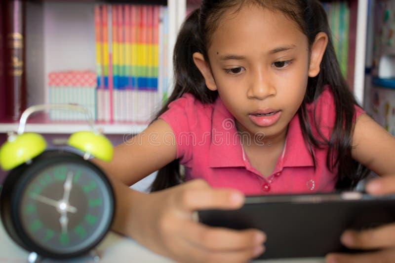 Liten flicka som hemma använder mobiltelefonen arkivfoto