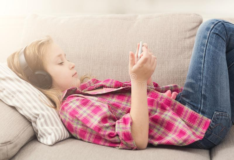Liten flicka som hemma använder smartphonen på soffan arkivbild