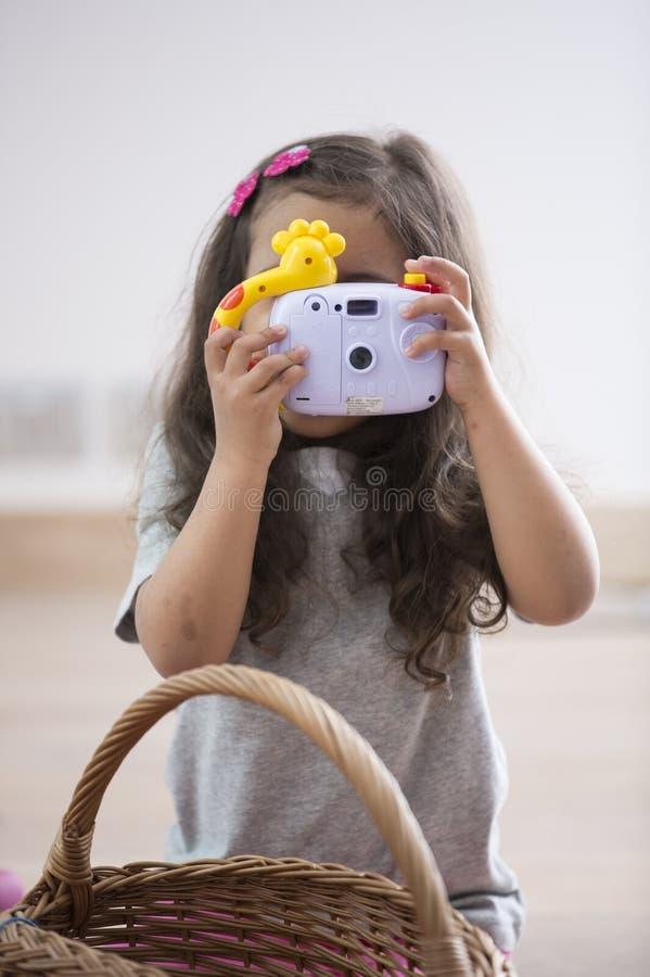 Liten flicka som hemma fotograferar till och med leksakkamera royaltyfria bilder