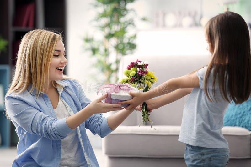Liten flicka som hemma ger gåva till hennes moder arkivbild