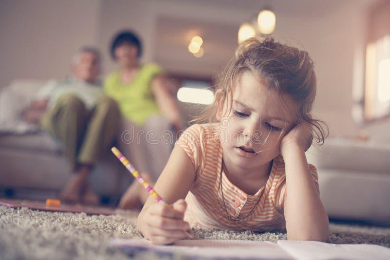 Liten flicka som hemma skriver fotografering för bildbyråer