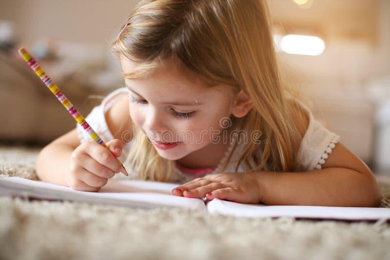 Liten flicka som hemma skriver royaltyfri fotografi