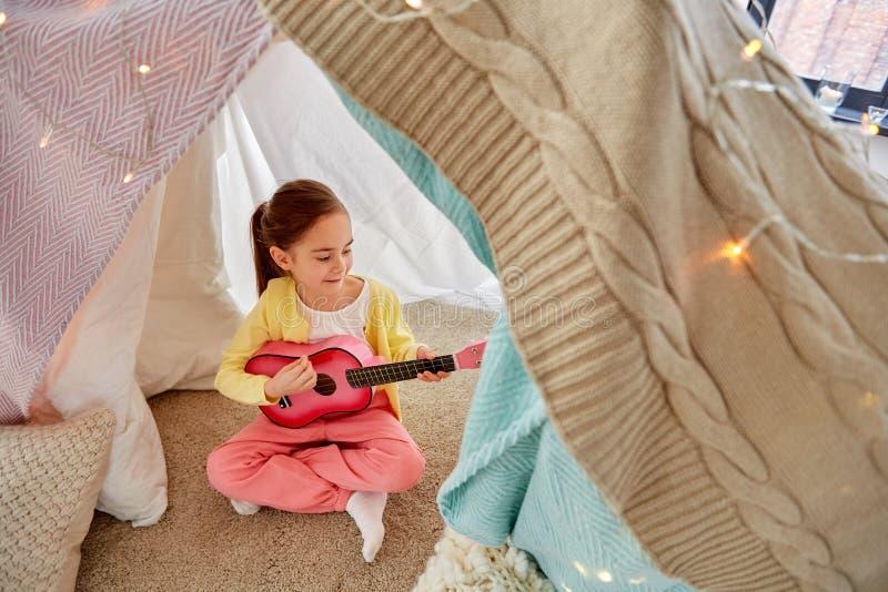 Liten flicka som hemma spelar gitarren i ungetält arkivfoton