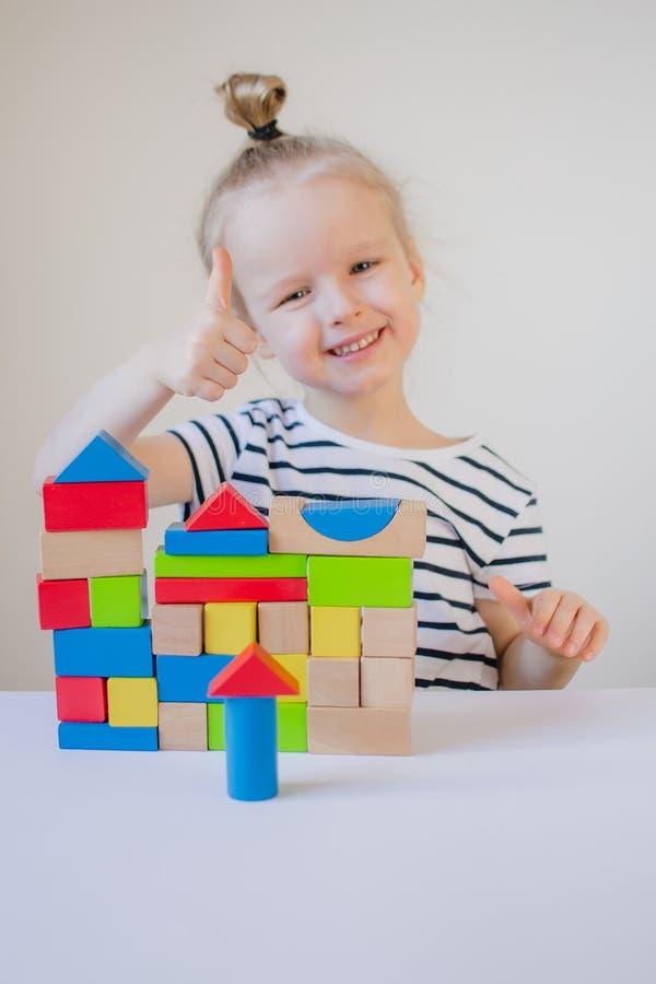 Liten flicka som hemma spelar med träfärgrika kuber royaltyfri bild