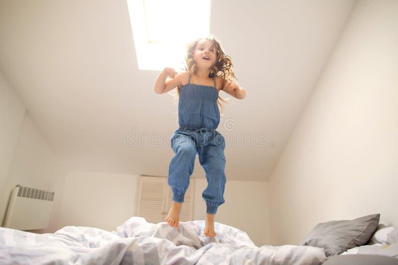 Liten flicka som hemma spelar och hoppar royaltyfri fotografi