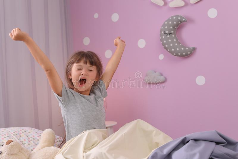 Liten flicka som hemma sträcker i säng sömntid till royaltyfria foton