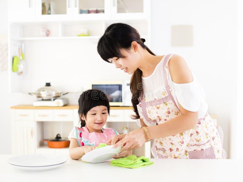 Liten flicka som hjälper hennes moderrengöringmaträtt i köket royaltyfri bild