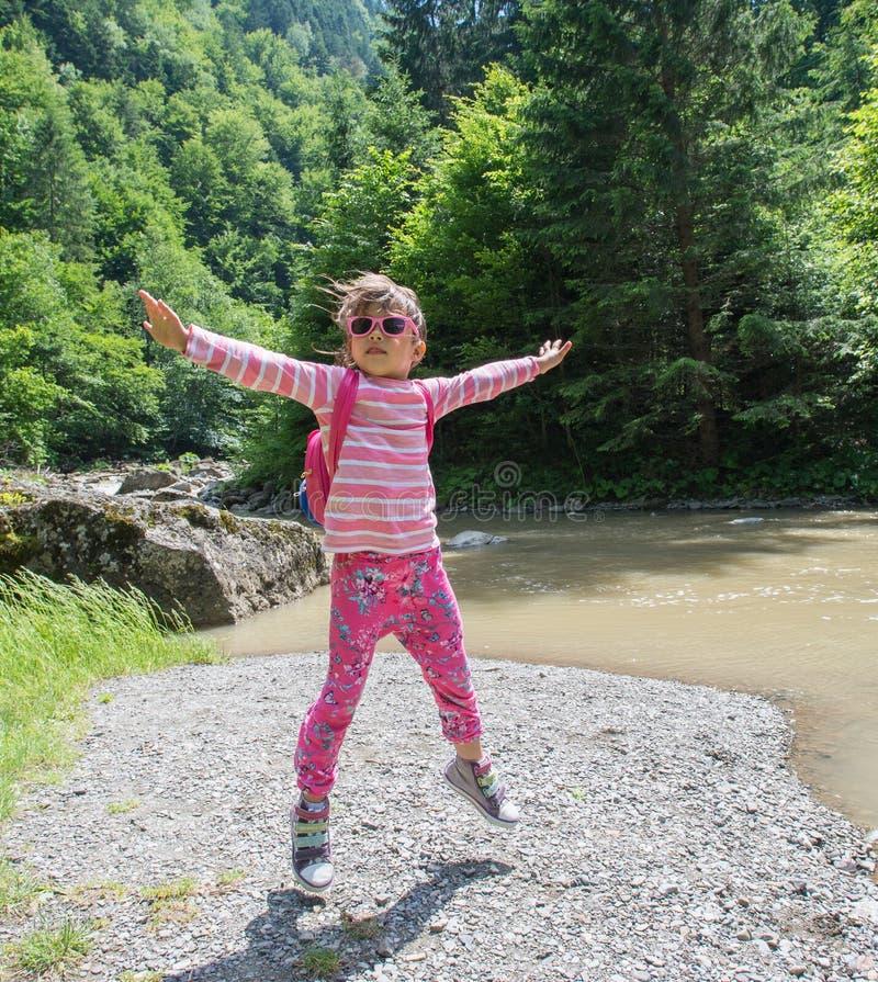 Liten flicka som hoppar i naturen arkivbild