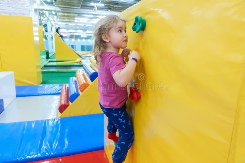Liten flicka som inomhus klättrar en vaggavägg royaltyfri fotografi