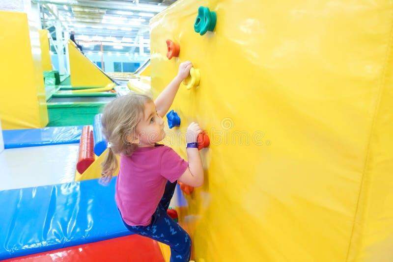 Liten flicka som inomhus klättrar en vaggavägg royaltyfria foton