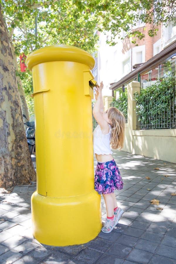 Liten flicka som kastar en bokstav i en brevlåda på gatan arkivbilder