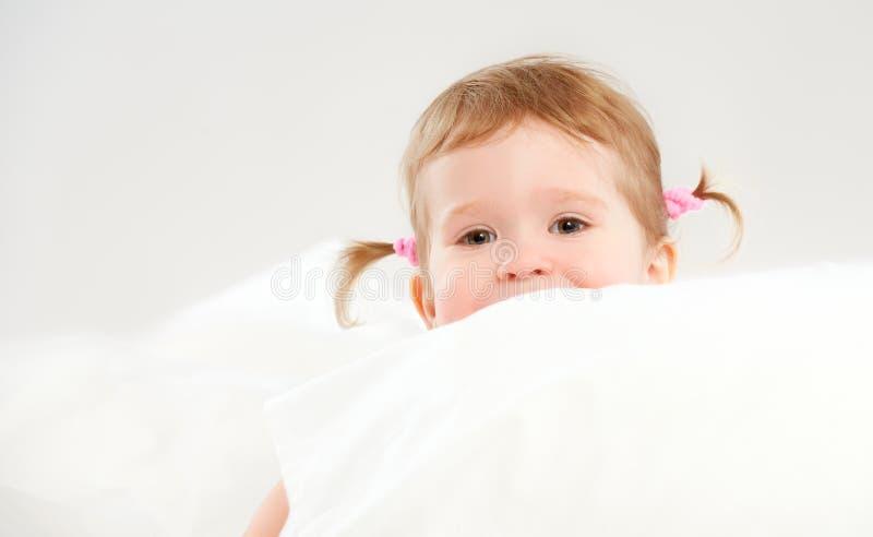Liten flicka som kikar från av kuddar i säng arkivfoton