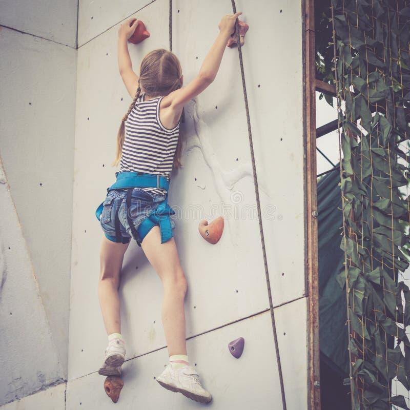 Liten flicka som klättrar en utomhus- vaggavägg fotografering för bildbyråer