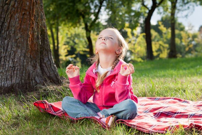 Liten flicka som kopplar av i yoga, poserar på gräs royaltyfri foto