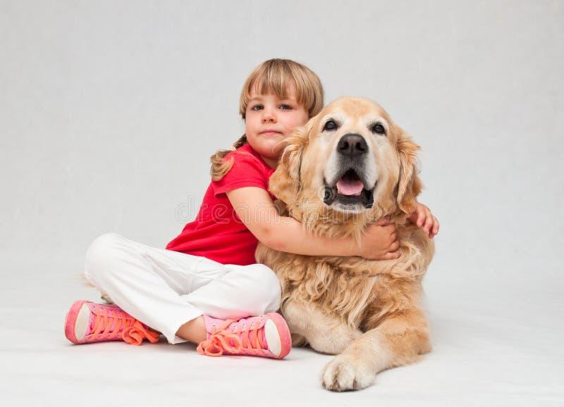 Liten flicka som kramar den stora golden retrieverhunden arkivbilder