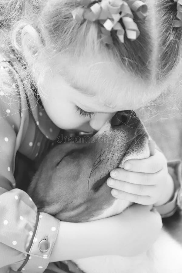 Liten flicka som kramar en basenjihund Svartvit bild royaltyfri fotografi