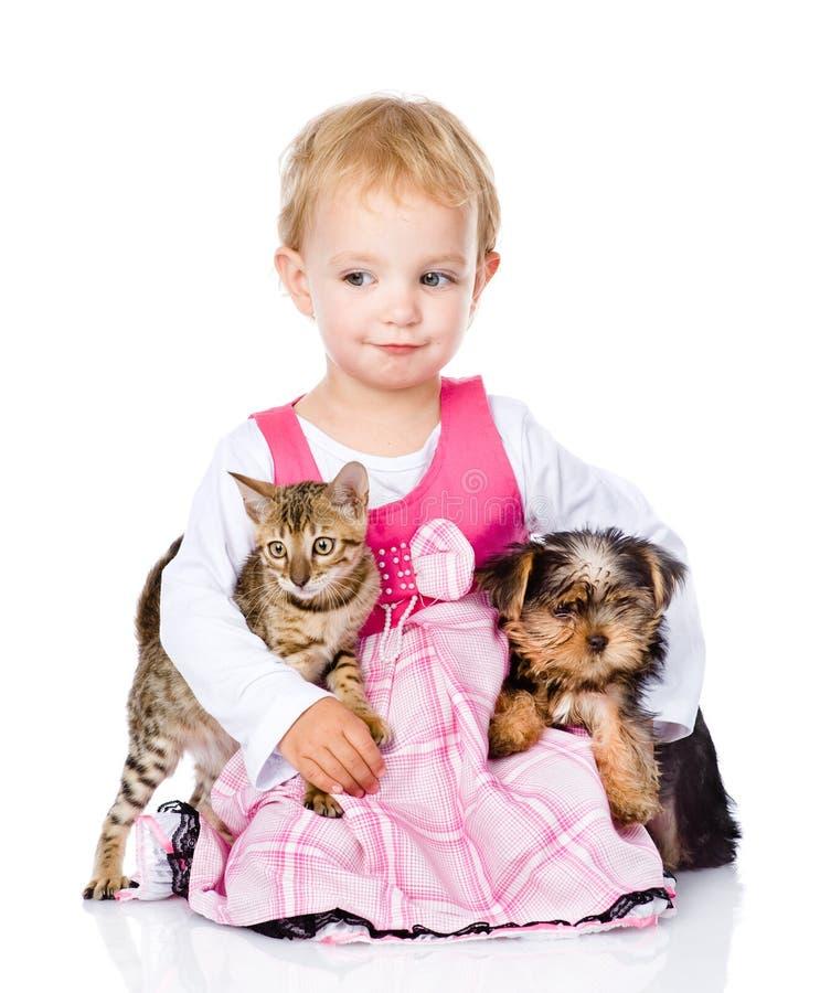 Liten flicka som kramar en kattunge och en valp arkivbild