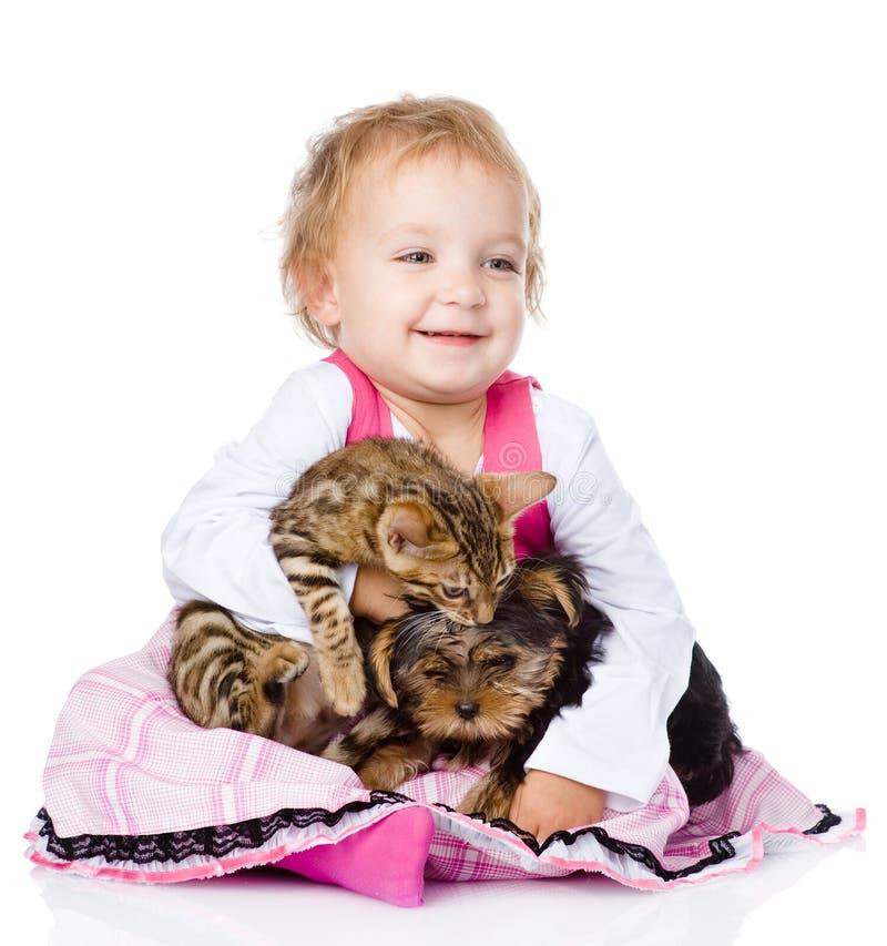 Liten flicka som kramar en kattunge och en valp Isolerat på vit royaltyfri fotografi