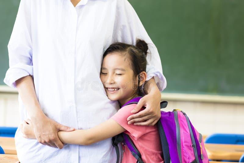 Liten flicka som kramar hennes moder i klassrum royaltyfria bilder