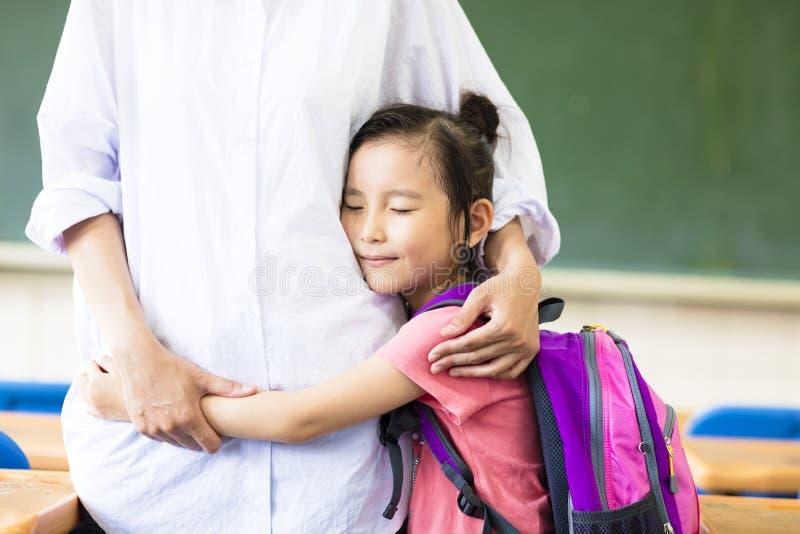 Liten flicka som kramar hennes moder i klassrum arkivfoto
