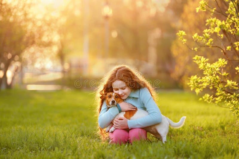 Liten flicka som kramar hennes v?n en hund i det fria arkivbilder