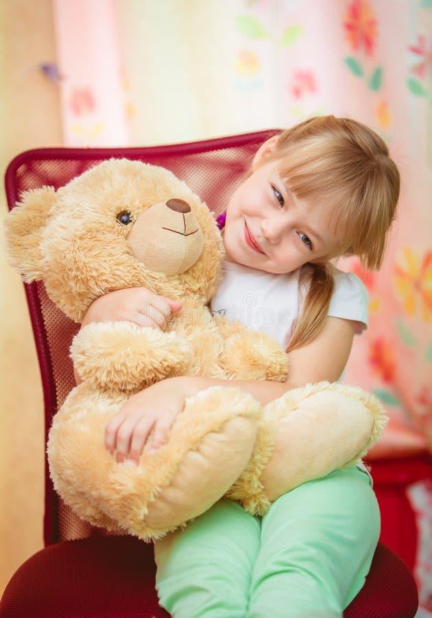 Liten flicka som kramar nallebjörnen royaltyfria foton