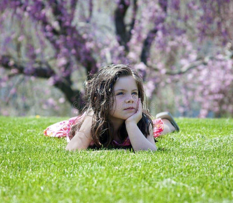 Liten flicka som lägger i gräset arkivfoto