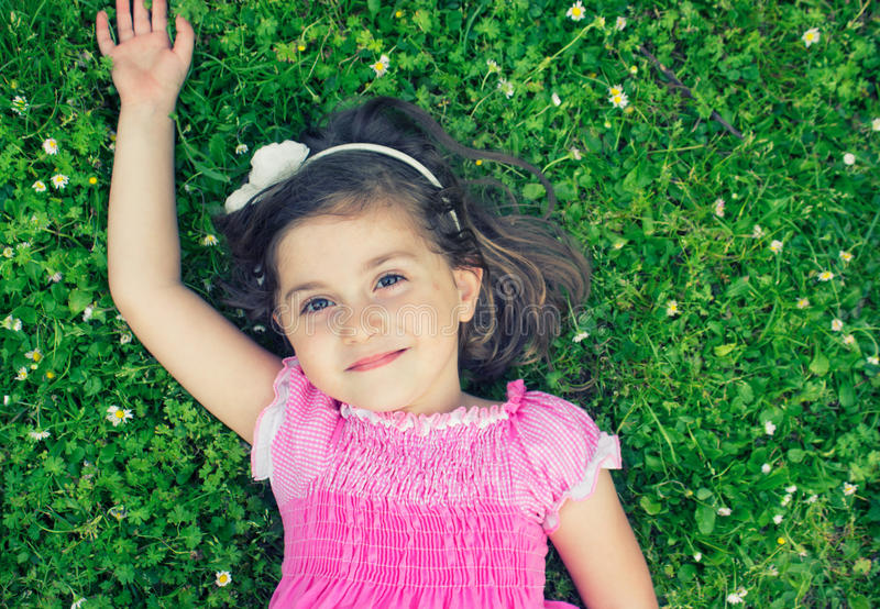 Liten flicka som lägger i gräset arkivfoton