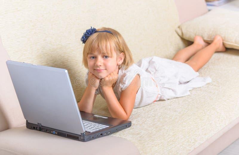 Liten flicka som lägger på soffan med bärbara datorn arkivbilder