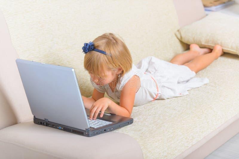 Liten flicka som lägger på soffan med bärbara datorn arkivfoto