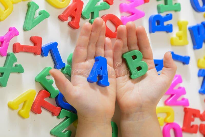 Liten flicka som lär alfabetbokstäver arkivbild