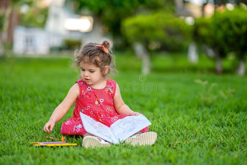 Liten flicka som lär för att färga eller att dra målarfärg på grönt gräs i natur på trädgården royaltyfri fotografi