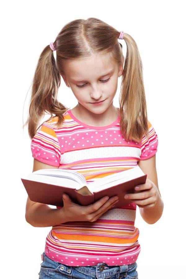 Liten flicka som läser en bok. arkivfoton