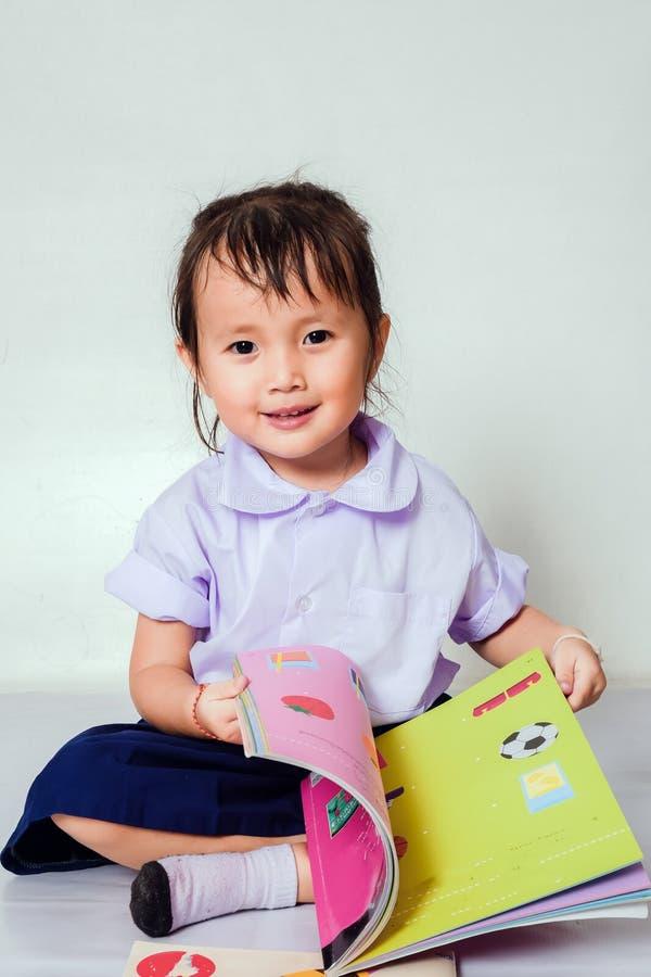 Liten flicka som l?ser en bok henne b?rande f?rskole- skolalikformig i hem royaltyfria foton