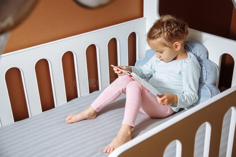 Liten flicka som läser en bok i sovrummet royaltyfri bild