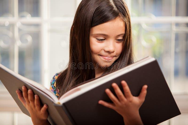 Liten flicka som läser en stor bok arkivbild