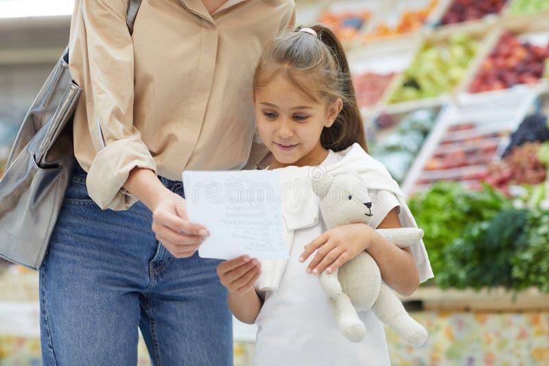 Liten flicka som läser shoppinglistan royaltyfria foton