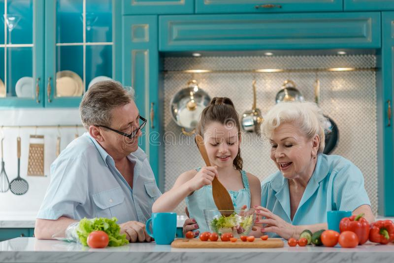 Liten flicka som lagar mat en sallad arkivfoto