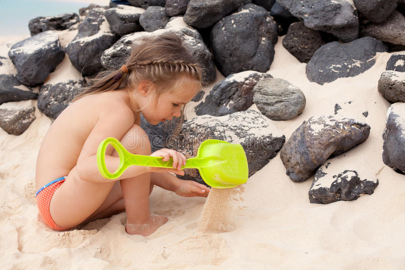 Liten flicka som leker med sanden arkivbilder
