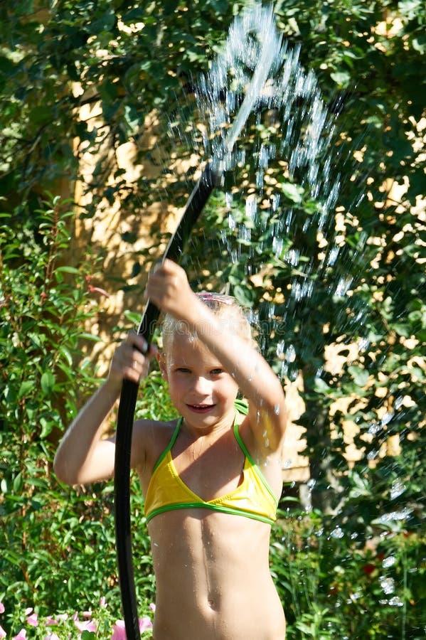 Liten flicka som leker med vatten arkivbild