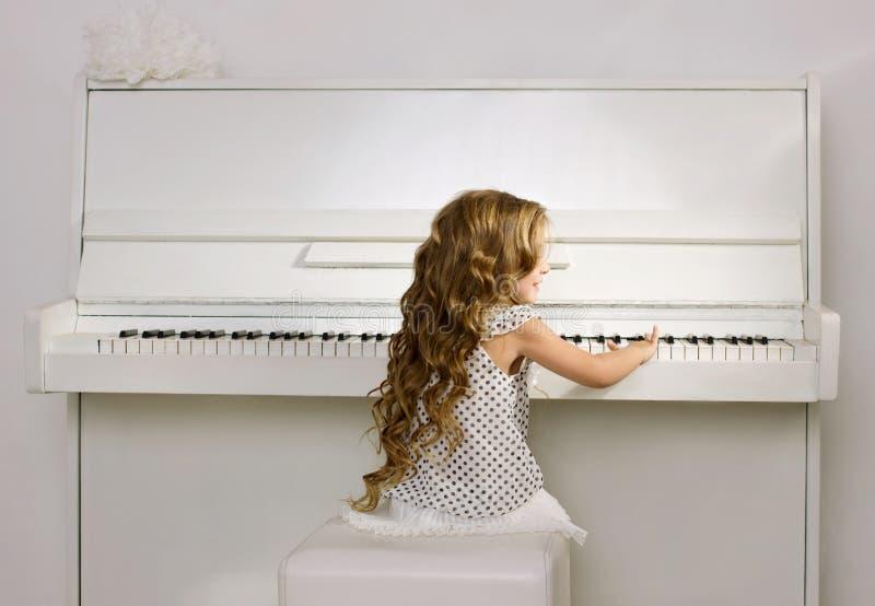 Liten flicka som leker pianot arkivfoto